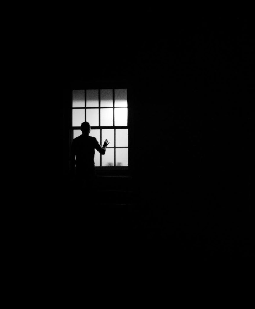 Photo en noir et blanc d'un homme regardant par une fênetre