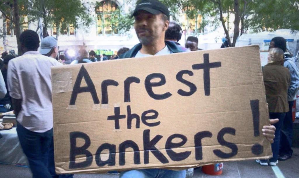 """Manifestant tenant une pancarte """"Arrêtez les banquiers !"""""""
